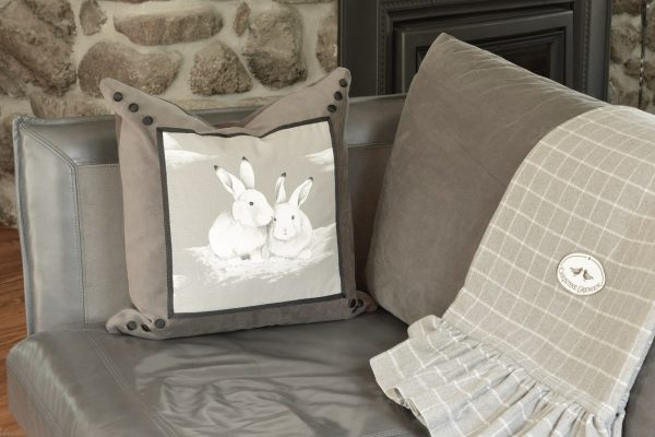 My rabbit friends cushion with the gray Frisson throw on a gray sofa.