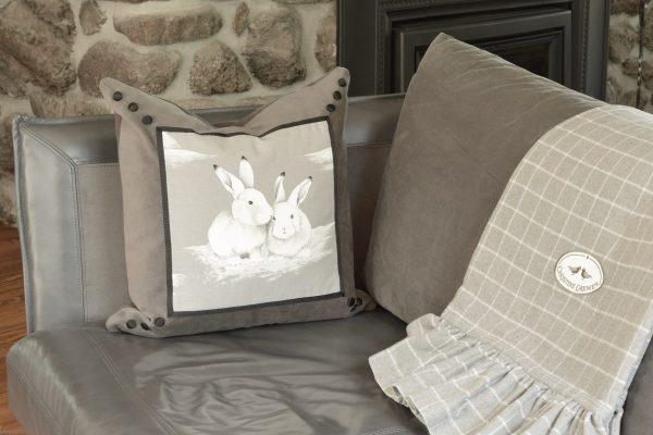 Coussin Mes amis lapins avec le jeté Frisson gris sur un canapé gris.