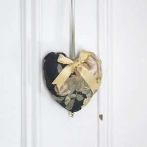 Coeur suspendu à une porte. Coeur en tissu vert foncé imprimé de motif floral or avec une boucle de ruban de satin or.