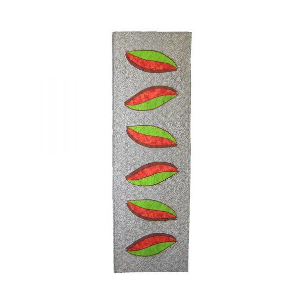 Pièce d'art textile format chemin de table. Courtepointe avec des feuilles vertes et oranges appliquées sur un fond noir et blanc. Les feuilles sont bordées par une ombre brune.