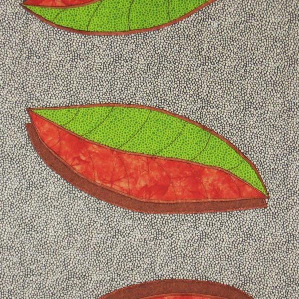 Détail de la pièce d'art textile Côte à côte. Feuille en appliqué où l'on voit le tissu vert, le tissu orange de la feuille et le tissu brun de l'ombre brodés au point de satin.