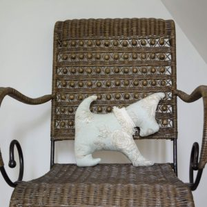 Small dog-shaped cushion on a rattan chair, The dog is in green fabric printed with ivory and brown flowers with an ivory fringe necklace.