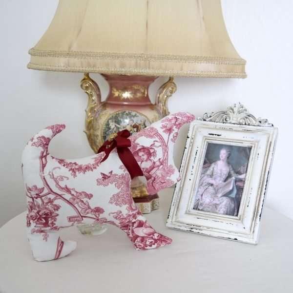 Chien Adélaïde dans un décor, sur une table devant une lampe et un cadre de style Renaissance.