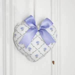 Heart in a fabric printed with a lattice of flowers with a rose in the center, lavender-blue on a white background. Blue ribbon bow with pearls.