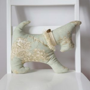 Small cushion terrier dog shape in green fabric with ivory and brown vine, grapes and flowers motifs.