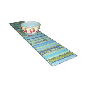 View of table runner Blue Lagoon with fruit bowl. Quilt made with strips of fabrics.