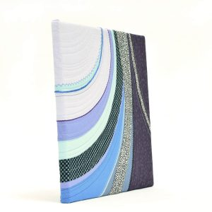 Perspective view of the textile art canvas Moraine. Curved fabric parts with decorative stitches.