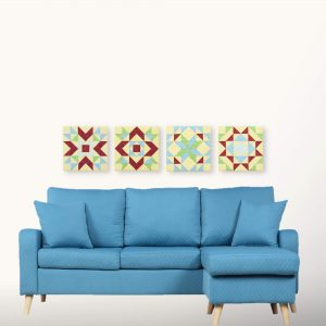 Textile art canvas Quadrille in a decor. Four quilt block tables above a blue sofa on a white wall.