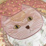 Détail du coussin Ronronnet où l'on voit la face brodée d'un chat avec de grands yeux or sur un tissu de satin corail.