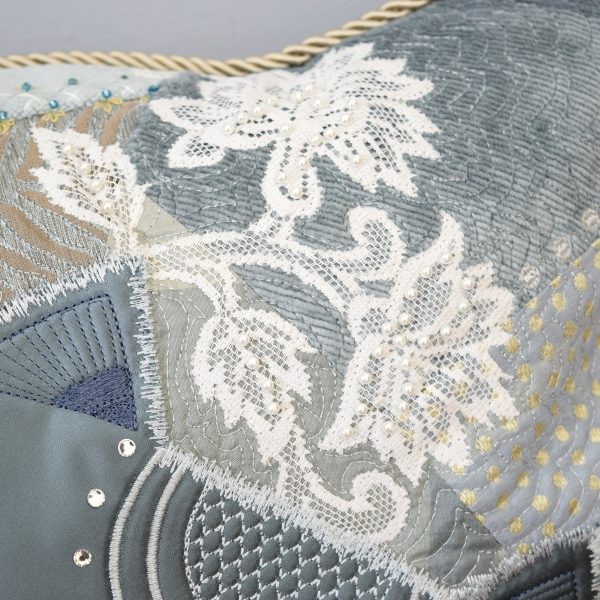 Detail of the textile art cushion Sybelle. White lace flower with white beads.