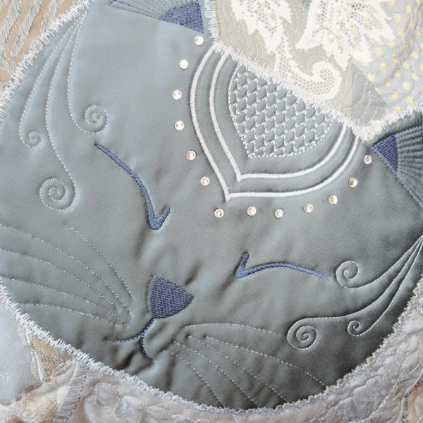 Detail of the textile art cushion Sybelle. Face of a sleeping cat. Light blue satin embroidered with swarovski stones.