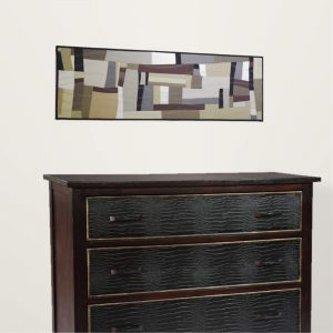 Piece of textile art A day will be seen in a setting above a black dresser.