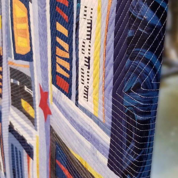 Détail de la pièce d'art textile Vous êtes ici. Vue du côté du tableau en perspective. Les tissus et le piquage se poursuivent jusqu'à l'arrière.