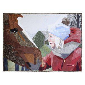 Pièce d'art textile La rencontre. Une fille à droite avec une tuque bleue et un manteau rouge en face d'un cheval à gauche.