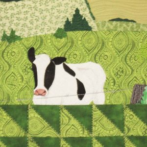 Detail of the piece of textile art The 3rd road. White and black cow in foreground on the edge of the fence.