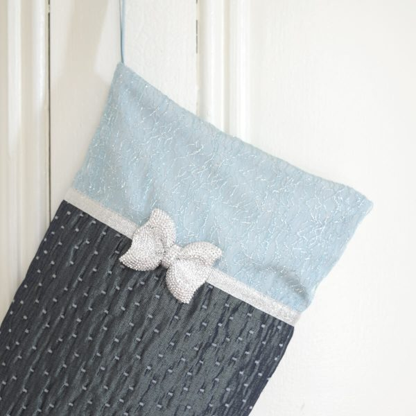 Detail of the Christmas stocking Sparkle, pale turquoise textured rim with ribbon and silver buckle, dark turquoise textured fabric leg.