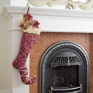 Christmas stocking Lady Guinevere hanging from a fireplace and decorated with Christmas accessories.