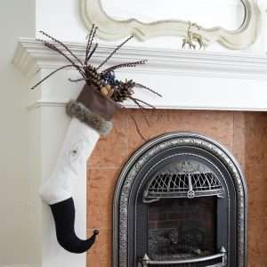 Navy Moon Elf stocking hanging from a fireplace and garnished with fir-cones and branches.