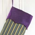 Detail of Christmas stocking Farandole, purple serrated lapel with small red bells.