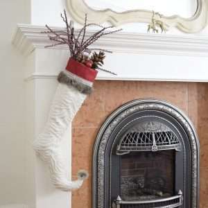 Elf stocking Frimas with decorative accessories, hanging from a fireplace.
