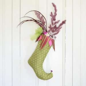 Christmas stocking Praline in chartreuse green and pink fabric ornated with Christmas decorations.