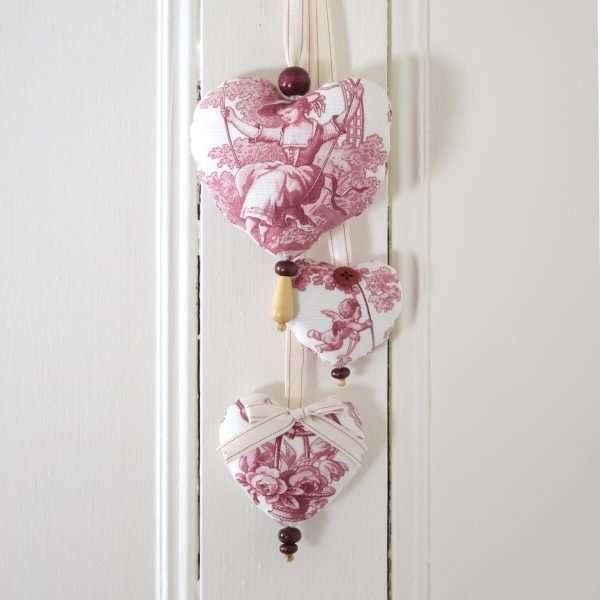 Trio de coeurs en tissu toile de Jouy rouge et blanc avec perles de bois, suspendu sur une porte blanche.