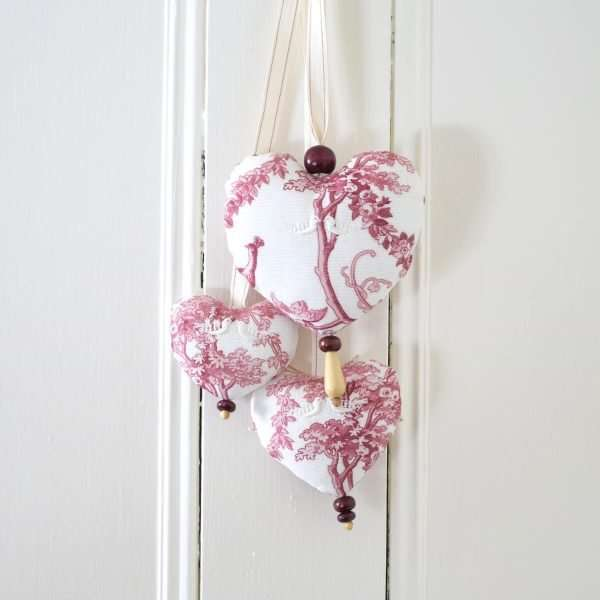 Trio de coeurs en toile de Jouy rouge sur fond blanc. Motifs floraux, perles de bois.