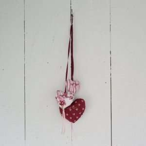 Three stuffed hearts hanging on an old wooden door. Hearts in flowery fabric and striped pink with embroidered birds.