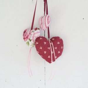 Three hearts in red and pink floral fabric hanging on a white wooden door
