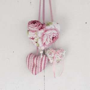 A trio of floral pattern fabric hearts and pink and white stripes.