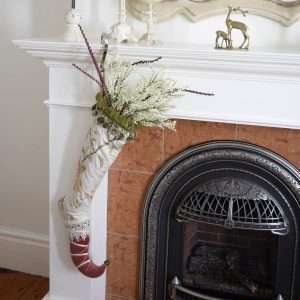 Elf stocking Lady Grandiflora trimmed with branches and white flowers, hanging on a fireplace.