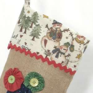 Detail of Christmas stocking Let it Snow, printed fabric lapel with snowmen and red ric-rac.