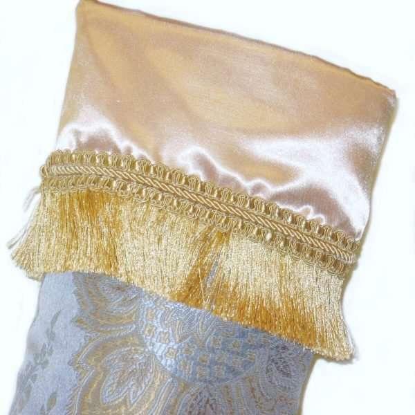 Détail du bas de Noël Louis XVI, revers en satin or avec frange dorée.