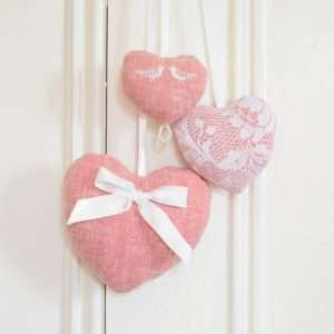 Hanging trio of hearts in pink fabric with lace, beads and satin bow.