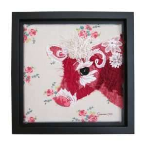 Textile art canvas Florette, a portrait of a red cow on a flower print background in a black frame.