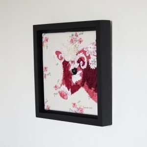 Textile art canvas, a portrait of a red and white cow on an ivory background with pink flowers. Framed canvas.