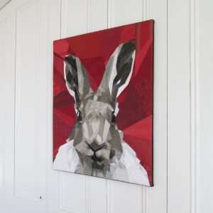 Textile art canvas Nice to meet you. Portrait of a hare on a red background.