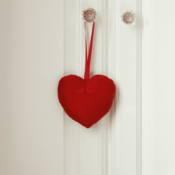 Red fabric heart hanging from the handle of a door.
