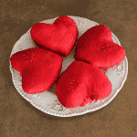 Four red silk hearts in an ivory plate.
