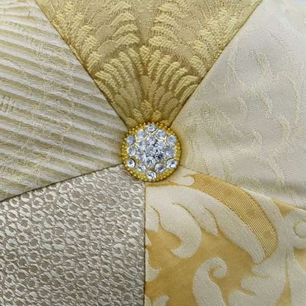 Detail of the star cushion Adara I, gold jewel with stones.
