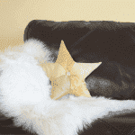 Gold star cushion Adara I on a brown leather sofa with sheepskin.