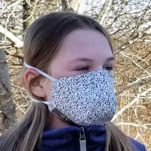 Cotton protective mask printed with gray flowers on a white background.