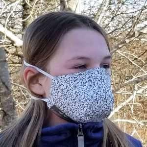 Masque de protection en coton imprimé de fleurs grises sur fond blanc.