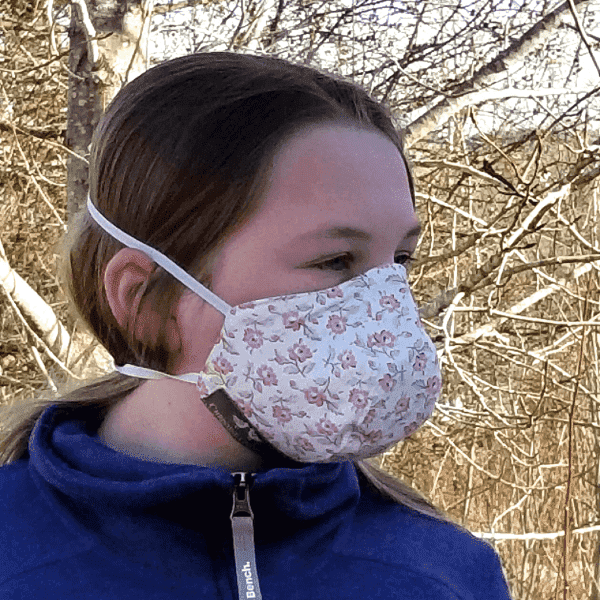 White cotton protective mask with pink flowers held by elastic bands behind the head.