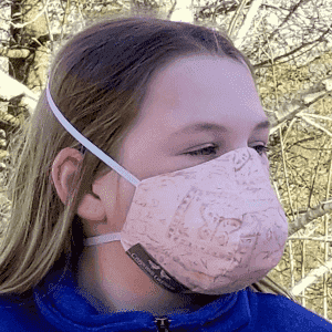 Girl wearing a cotton protective mask with small pink patterns