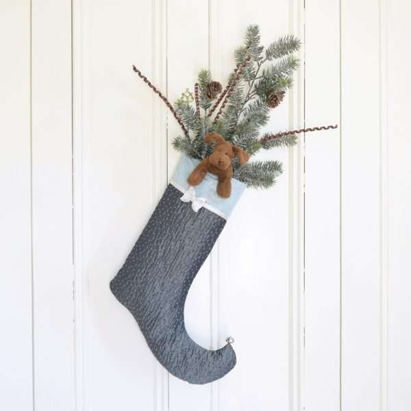 Turquoise Christmas stocking decorated with plush and branches